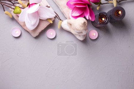 Photo for Burning candles, Buddha, towels  and pink magnolia flowers on grey textured background. Spa concept. Selective focus. Place for text. Flat lay - Royalty Free Image