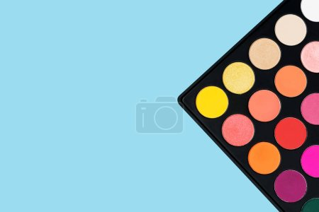 Black plastic palette of brightly coloured yellow, red, pink, orange eyeshadow placed in the corner of pastel baby blue background shot with studio light from above