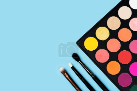 Black plastic palette of brightly coloured yellow, red, pink, orange eyeshadow and three make-up brushes of various types arranged in the corner of pastel baby blue background shot with studio light from above