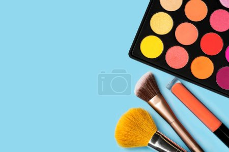 Black plastic palette of brightly coloured yellow, red, pink, orange eyeshadow, orange liquid lipgloss, and two make-up brushes arranged in the corner of pastel baby blue background shot with studio light from above