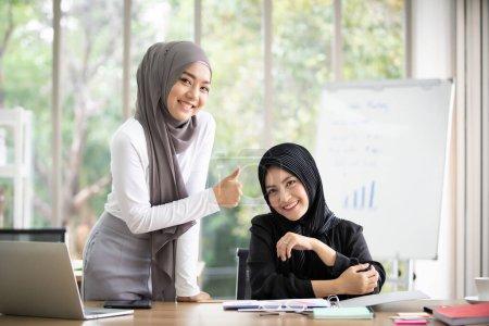 Asiatique jeune femme d'affaires musulmane travaillant ensemble dans le bureau. Succès dans le cheminement de carrière de la femme d'affaires musulmane. Conjoint professionnel et concept de travail d'équipe dans les gens modernes.