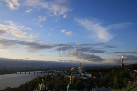 Kiev Pechersk Lavra with Motherland statue on hill of Dnieper river at sunset