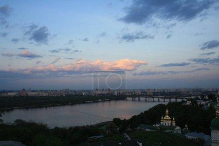 Kiev Pechersk Lavra on hill of Dnieper river on background at sunrise