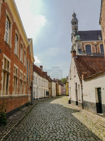 Narrow street with old houses and the St. Margaret's church in the Unesco protected beguinage in the city center of Lier; Belgium