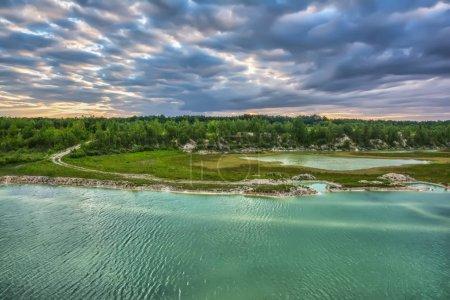 Photo pour Beau coucher de soleil sur le lac. Forêt sur la rive, ciel avec nuages dessus. - image libre de droit