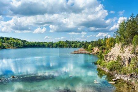 Photo pour Journée ensoleillée sur le lac de basalte. Forêt sur le rivage, les rochers, ciel bleu avec des nuages au-dessus d'eux. - image libre de droit