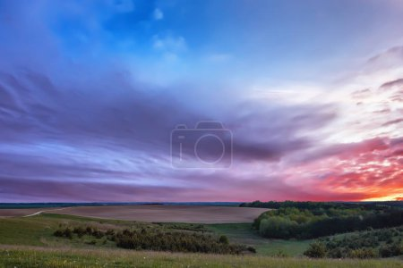 Photo for Meadows, plowed field and forest at sunset with beautiful clouds. - Royalty Free Image