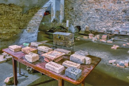 Photo for Ancient bricks on a wooden table and a chest on the floor in a medieval catacomb. - Royalty Free Image