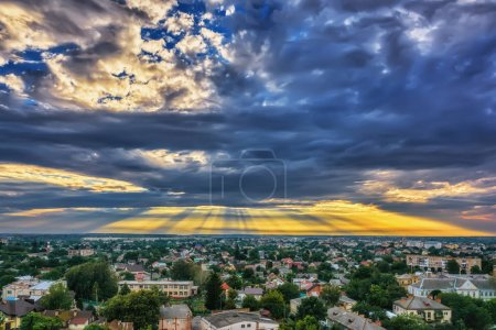 Photo for Sky with clouds and rays of the sun over evening city at sunset. - Royalty Free Image