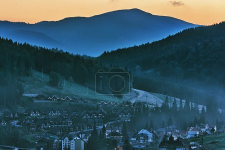 Photo for Evening in forested mountains, a small resort town in a valley covered with fog. - Royalty Free Image
