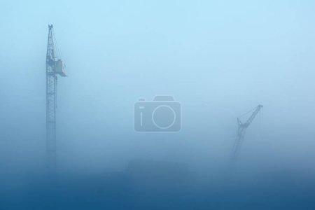 Photo pour Grues à tour dans le brouillard. - image libre de droit