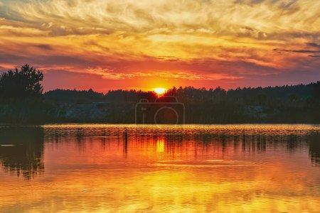 Photo pour Coucher de soleil sur la rive d'un lac de la forêt. Le ciel avec nuages se reflète dans l'eau. - image libre de droit