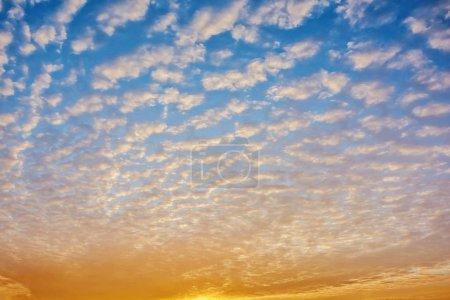Photo pour Coucher du soleil, de petits nuages dans le ciel bleu. - image libre de droit