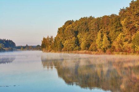 Photo pour Lever du soleil sur le lac - la forêt sur la rive se reflète dans l'eau. - image libre de droit