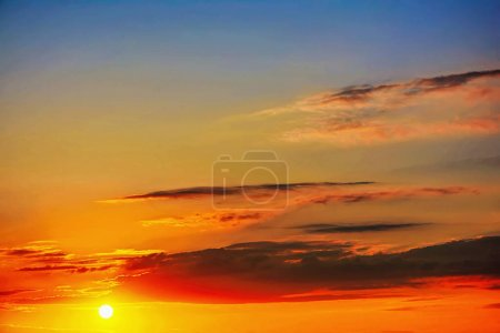 Photo for Sun at sunrise sunset with clouds on a blue sky. - Royalty Free Image