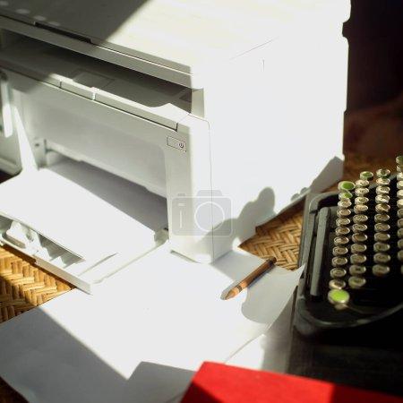 Photo pour Machine à écrire rétro et une imprimante moderne placées sur une table - image libre de droit