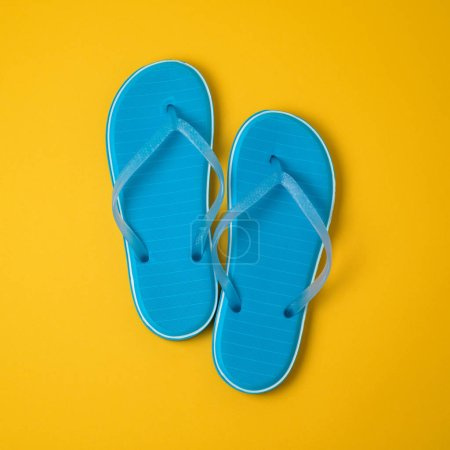 Minimal summer concept. Blue flip flops over yellow background. View from above