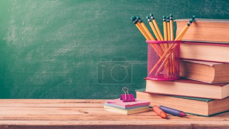 Photo for Back to school background with pencils and old books over chalkboard - Royalty Free Image