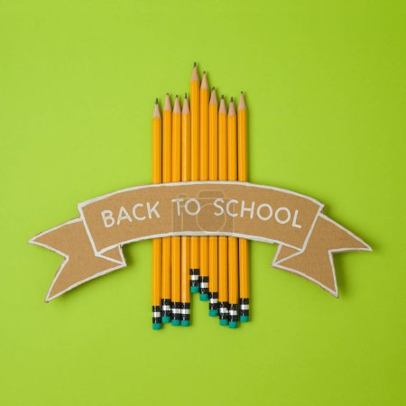 Back to school minimal concept with pencils and cardboard banner. View from above