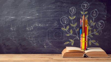 Photo pour Retour à fond l'école avec l'éducation arbre issu de crayons et de vieux livre sur tableau noir - image libre de droit