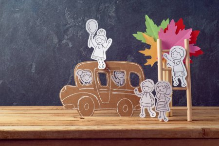 Back to school concept with small children doodles and school bus over table background
