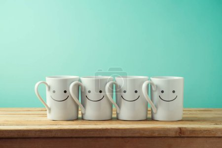 Coffee cups with funny faces on wooden table. Friendship day celebration background