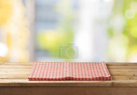 Photo for Empty wooden table with tablecloth over abstract bokeh background. Mock up for display or montage product - Royalty Free Image