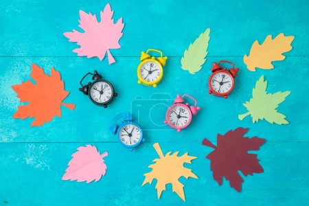 Fall back time change concept. Creative composition with alarm clocks and paper autumn leaves. Top view from above