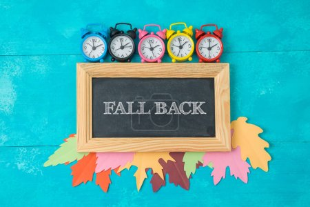 Fall back time change concept. Creative composition with alarm clocks, autumn leaves and chalkboard. Top view from above