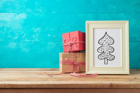 Photo for Christmas holiday background with pine tree drawing and gift boxes on wooden table - Royalty Free Image