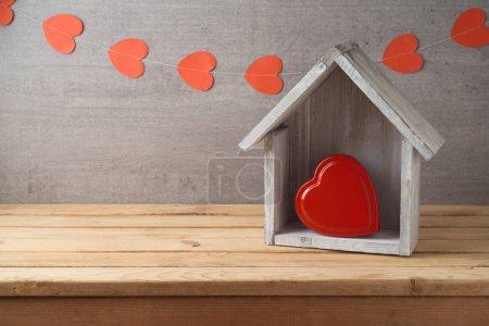 Photo pour Concept de Saint-Valentin avec boîte cadeau en forme de coeur et maison sur table en bois sur fond de guirlande - image libre de droit