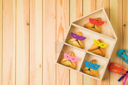 Jüdischer Ferienpurimhintergrund mit niedlichen lustigen Hamam-Plätzchen und Spielzeughaus auf Holztisch. Ansicht von oben. Kreative Purimkorbidee