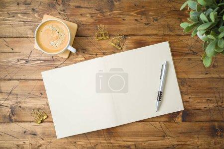 Photo pour Carnet scolaire avec tasse à café et plante sur table en bois. Vue de dessus - image libre de droit