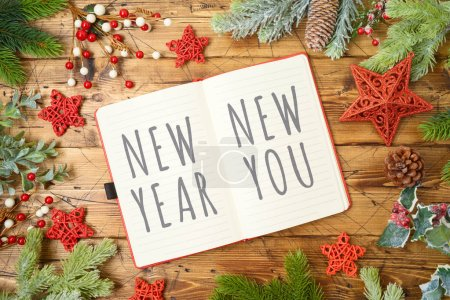 Photo for New Year resolutions concept with notepad and fir tree branches on wooden background. Top view from above. Flat lay - Royalty Free Image