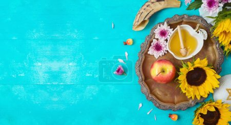 Photo for Jewish holiday Rosh Hashana background with honey, apples and sunflowers on blue wooden table. Top view from above - Royalty Free Image