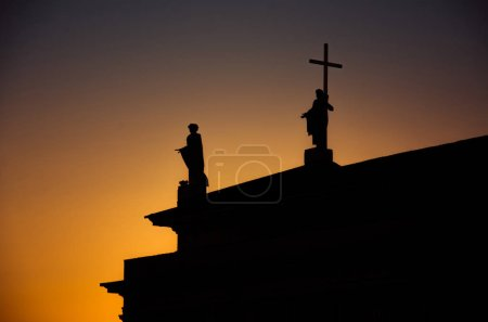 Silhouette of monuments on the roof of Cathedral Basilica Of St. Stanislaus and St. Vladislav on Cathedral Square with colourful evening sky on background at sunset, Vilnius, Lithuania