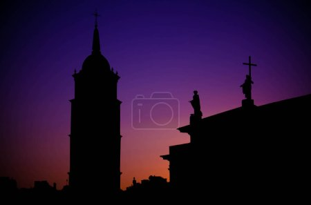 Silhouette of Bell Tower and monuments on the roof of Cathedral Basilica Of St. Stanislaus and St. Vladislav on Cathedral Square with colourful evening sky on background at sunset, Vilnius, Lithuania