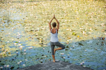 Photo for Woman practices yoga on a lake with lotus water lilies - Royalty Free Image