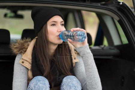 Photo pour Jeune femme buvant de l'eau d'une bouteille de boisson froide - image libre de droit