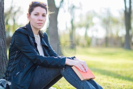 Photo for Young man with a backpack sitting on a bench in the park - Royalty Free Image
