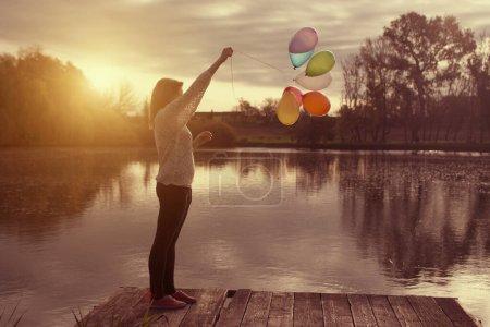 Photo pour Jeune femme avec ballon sur la plage - image libre de droit