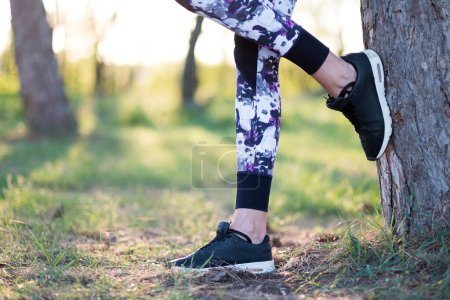 Photo pour Chaussures de sport femme au coucher du soleil - image libre de droit