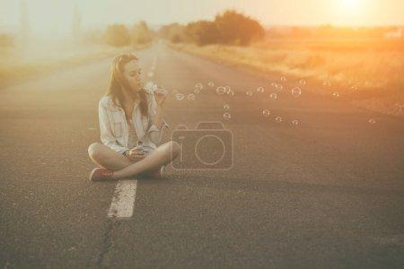 Photo pour Jeune femme assise sur l'herbe dans le parc - image libre de droit
