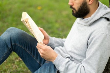 Photo for Man reading book on the grass in park - Royalty Free Image