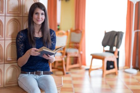 Photo for Woman reading a book indoor - Royalty Free Image