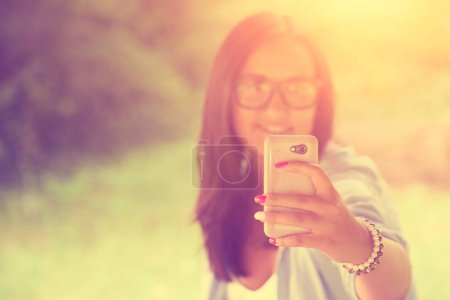 Photo for Young woman with smartphone in the park - Royalty Free Image