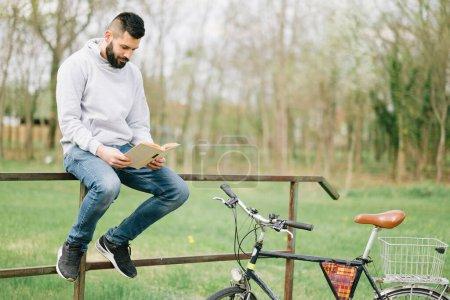 Photo pour Jeune homme avec vélo dans le parc - image libre de droit