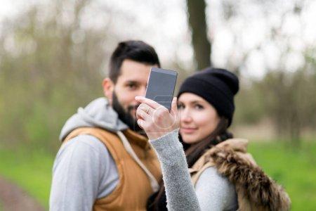 Photo pour Jeune couple prenant selfie avec smartphone dans le parc - image libre de droit