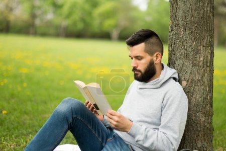 Photo pour Jeune homme lisant un livre dans le parc - image libre de droit