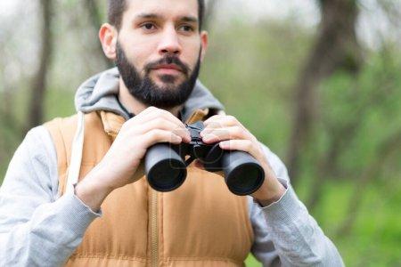 Photo pour Jeune homme aux jumelles dans la forêt - image libre de droit